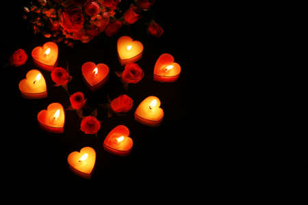 candles: Romantic atmosphere with candle lights and flowers on dark background Stock Photo