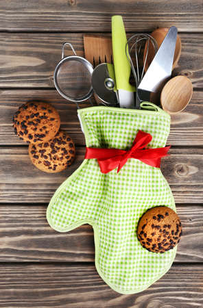 baking cookies: Set of kitchen utensils in mitten with chocolate cookie on wooden planks background