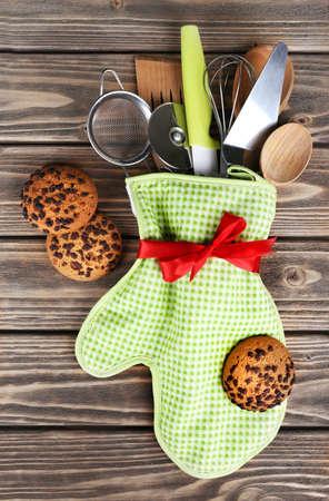 cookie baking: Set of kitchen utensils in mitten with chocolate cookie on wooden planks background