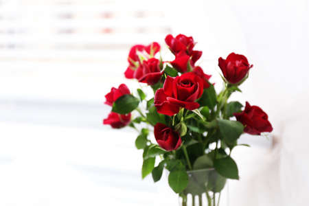 Bouquet of red roses in glass vase on curtain background photo