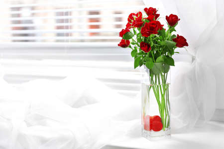 red roses: Ramo de rosas rojas en el florero de cristal con el corazón en el fondo alféizar Foto de archivo