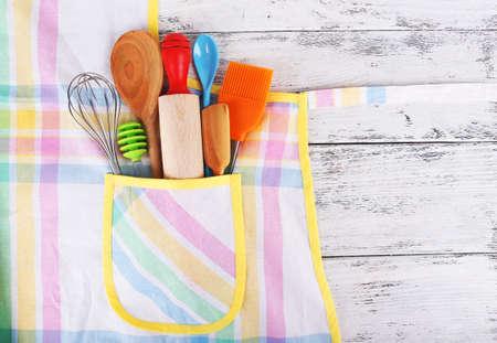 mandil: Conjunto de utensilios de cocina en el bolsillo del delantal sobre fondo de madera