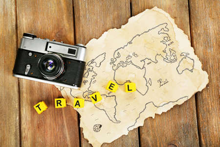 camera: Retro camera on world map with word Travel on wooden table background Stock Photo