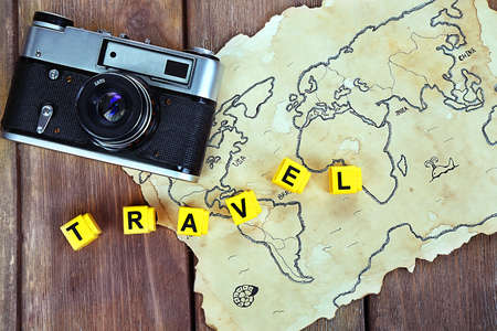 Retro camera on world map with word Travel on wooden table background photo