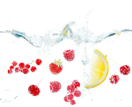 natural juices: Fresh fruits and berries splashing in water isolated on white Stock Photo