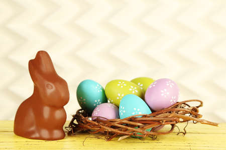 eastertime: Easter composition with chocolate rabbit on light background