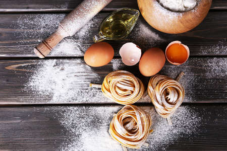 Raw homemade pasta and ingredients for pasta on wooden background Stock Photo