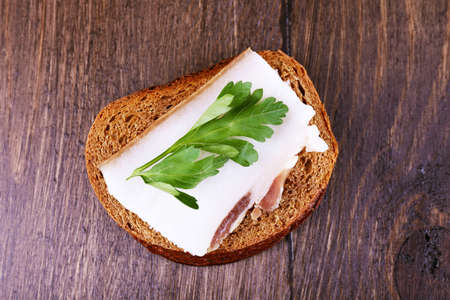 lard: Sandwich with lard and parsley on wooden background