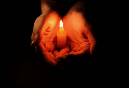 reverent: Candle in female hands on black background