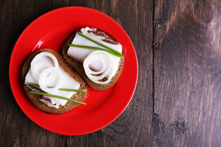 lard: Sandwiches with lard and onion on plate on wooden background