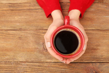 red morning: Female hands holding cup of coffee on wooden background