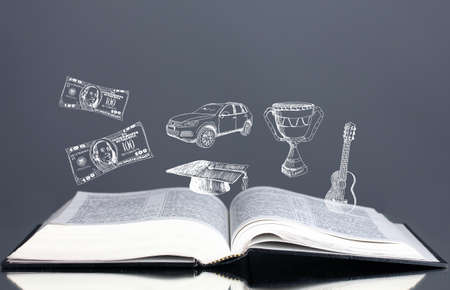 Open book with drawings on grey background photo