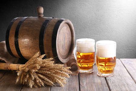 vasos de cerveza: Barril de cerveza con vasos de cerveza en la mesa