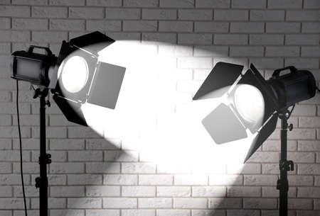 lighting background: Photo studio with lighting equipment on brick wall background
