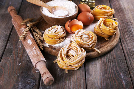 pasta: Raw homemade pasta and ingredients for pasta on wooden background Stock Photo