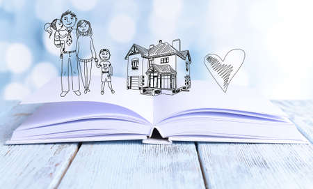Open book with drawings on light background photo