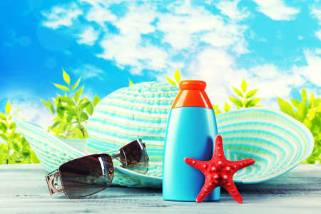 Bottle of suntan cream with sunglasses and hat on table isolated on white photo