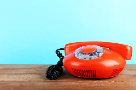 telefono antico: Retro apparecchio telefonico su tavola di legno su sfondo blu Archivio Fotografico