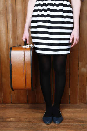 portmanteau: Woman holding old suitcase on wooden background