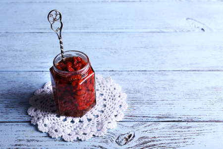 lace doily: Jar of goji berry jam on lace doily on wooden background Stock Photo