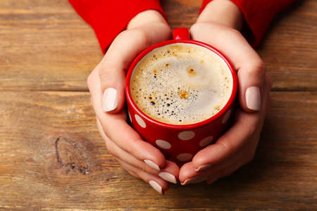 cold: Female hands holding cup of coffee on wooden background