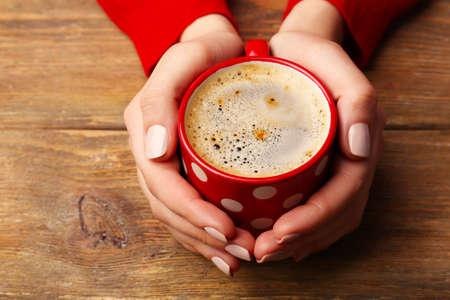 bebidas frias: Manos femeninas que sostienen la taza de café sobre fondo de madera Foto de archivo
