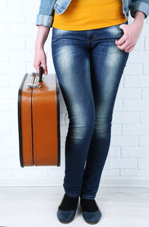 portmanteau: Woman holding old suitcase on brick wall background