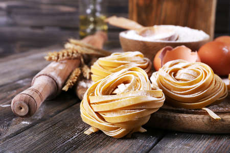noodle: Raw homemade pasta and ingredients for pasta on wooden  Stock Photo