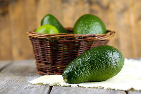 fruits in a basket: Avocado with limes in basket on wooden