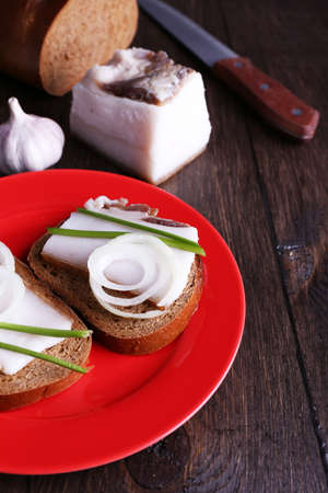 lard: Sandwiches with lard on plate and garlic on wooden