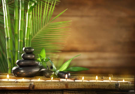 Spa stones, candles on wooden background