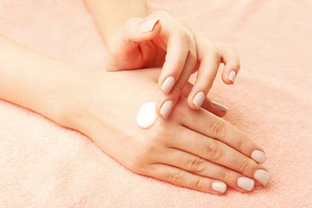 caring hands: Woman caring hands with cream on fabric background Stockfoto