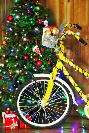 decorated bike: Bicicletta gialla vicino all'albero di Natale Archivio Fotografico