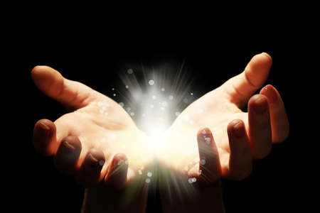 dando la mano: Luz en las manos del hombre en la oscuridad