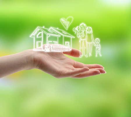 familia animada: Mano femenina con dibujos de la familia y de la casa en el fondo la naturaleza