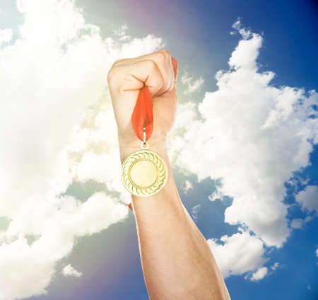 commendation: Golden medal in hand on sky background Stock Photo