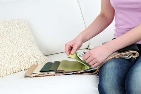 chooses: Woman sitting on sofa and chooses scraps of colored tissue Stock Photo