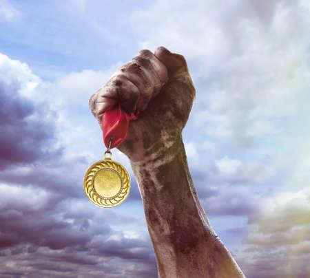 Golden medal in hand on sky background Reklamní fotografie