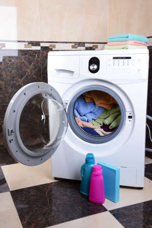 launderette: Washing machine loaded with clothes in bathroom Stock Photo
