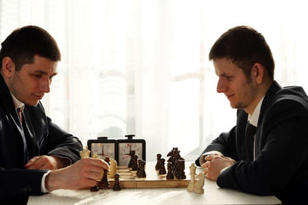 Two handsome businessmen playing chess in office