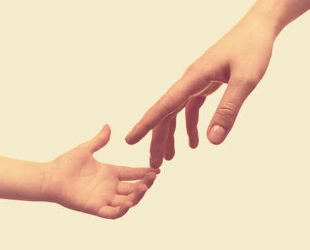 niños sosteniendo un cartel: Niño y la madre manos sobre fondo claro