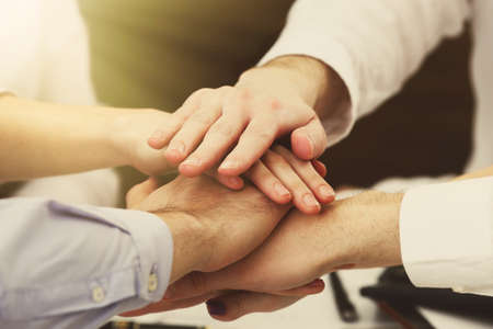 Mains Unies de l'équipe de l'entreprise sur l'espace de travail de fond