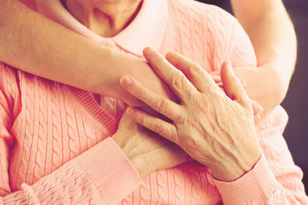 adult care: Old and young hands hug, closeup Stock Photo