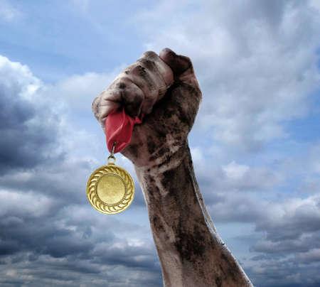 空の背景に手で黄金のメダル
