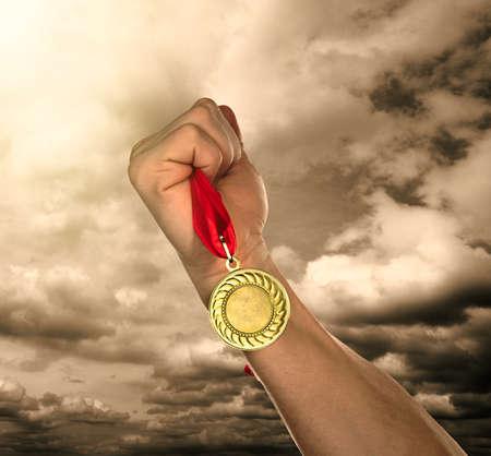空の背景に手で黄金のメダル 写真素材 - 42660849
