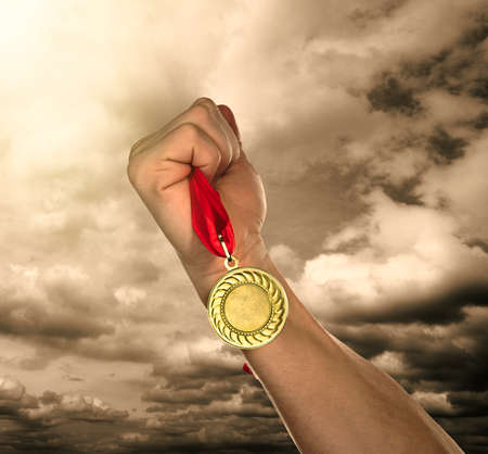 sports winner: Golden medal in hand on sky background Stock Photo