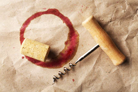 uncork: Wine stain, cork and corkscrew on crumpled paper background