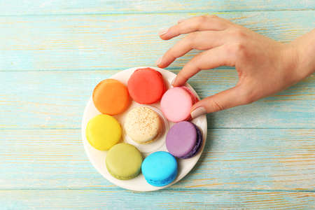 small plate: Female hand taking tasty colorful macaroons from small plate on color wooden background Stock Photo