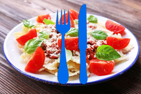 bolognese: Pasta bolognese with cherry tomatoes in white plate on wooden table, closeup