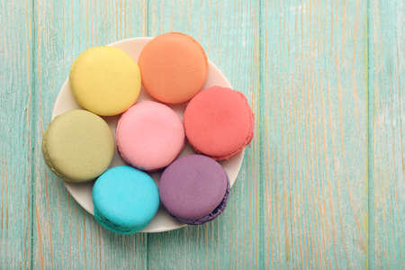 small plate: Tasty colorful macaroons in small plate on color wooden background Stock Photo